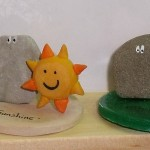 ornaments - pebble on clay base with a yellow fima sun