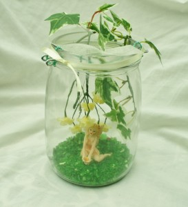 Glass jar with ivy and yellow flowers hanging down with a little dainty faery sitting on green glassbase