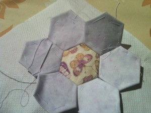 6 pale purple hexagons of fabric sewn around a middle yellow one. The yellow one has a purple butterfly on it.