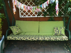 garden seat with green and brown covers and bunting hanging on yhe top rail