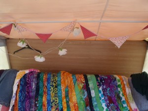 pink and red bunting and a multi colouted quilt.