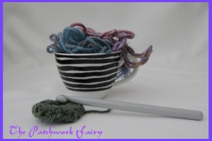 wool in a tea cup and a crochet hook