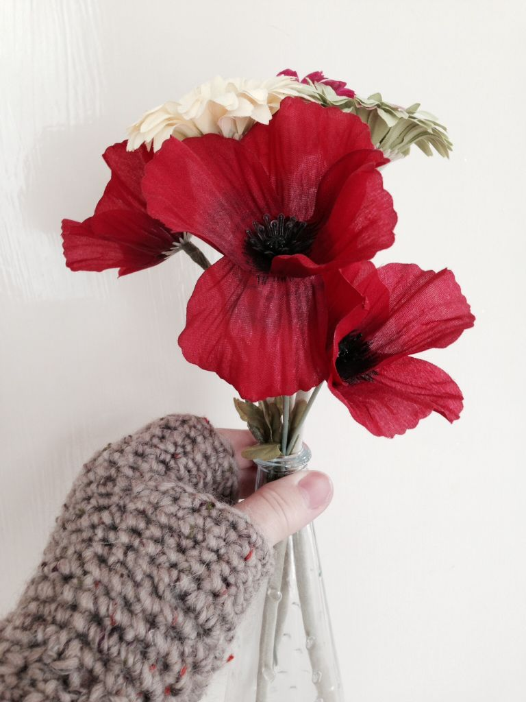 using fingerless gloves holding red flowers