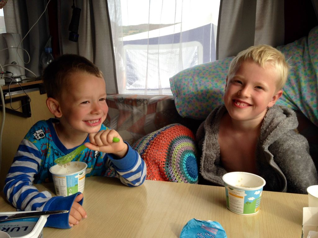 Grandsons sitting at table in caravan