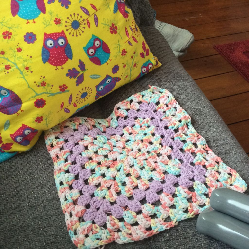 Yellow owl fabric cushion and crochet granny square in pink, cream, green and peach variegated cotton with two lilac rows.