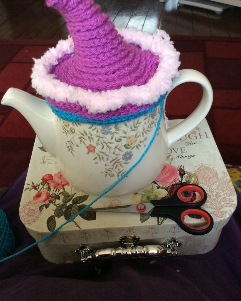 Crochet tea pot cover in purple and teal yarn