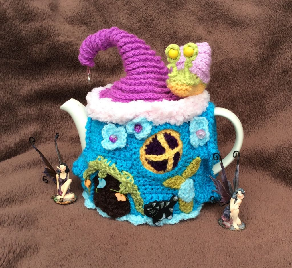 Crochet Tea Cosy in teal snd purple and pink in the shape of a Fairy House with flowers and Leaves sewn on.