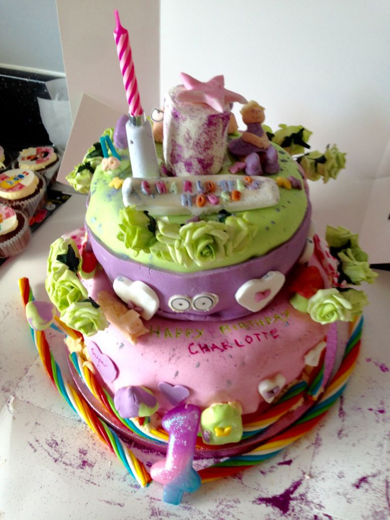 Pink and green and purple birthday cake in shape if a fairy castle