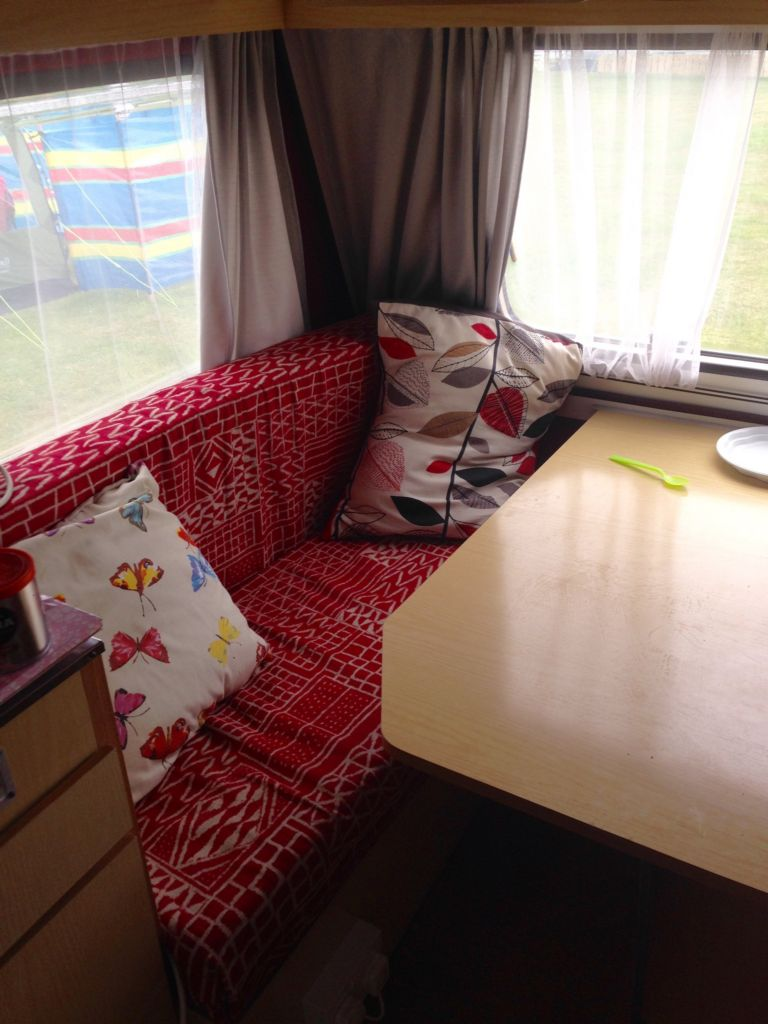 inside of small caravan showing red seats