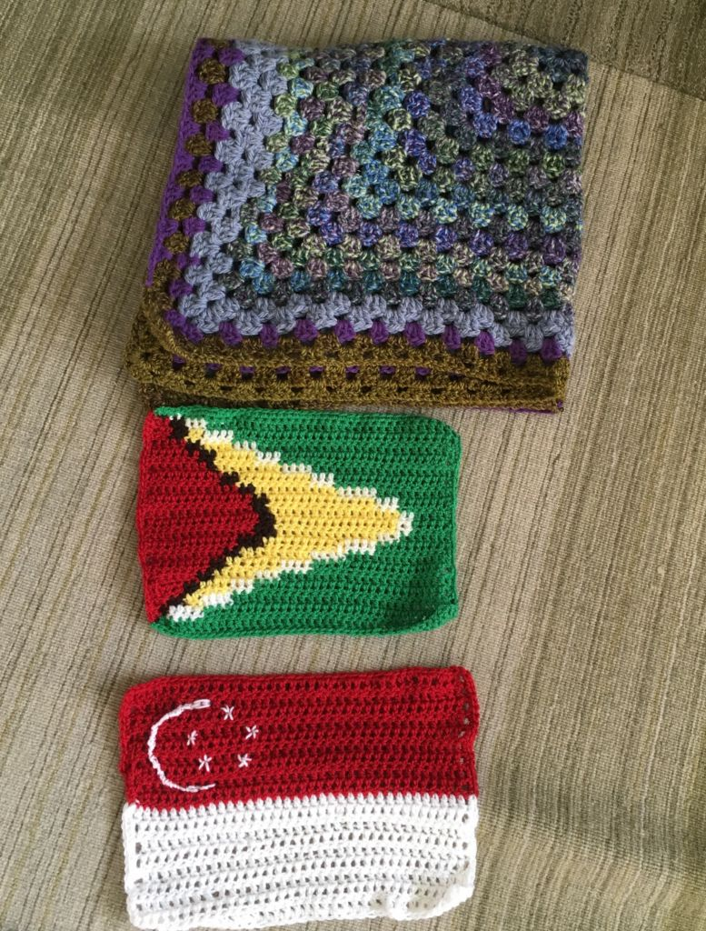 Crochet flag of Singapore and Guyana and a purple crochet blanket