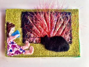 Fabric picture of a fire, a black cat and a girl sipping cup of tea.