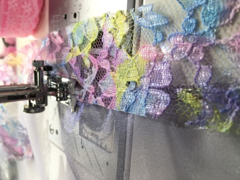 Pink, yellow, blue lace being sewn onto lilac gauze