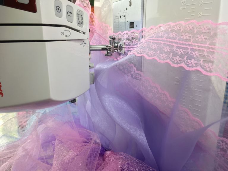 Pink lace being sewn onto lilac fairy dress