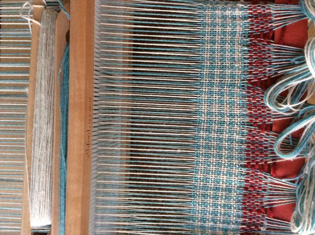 Weaving loom with blue and white houndstooth weave