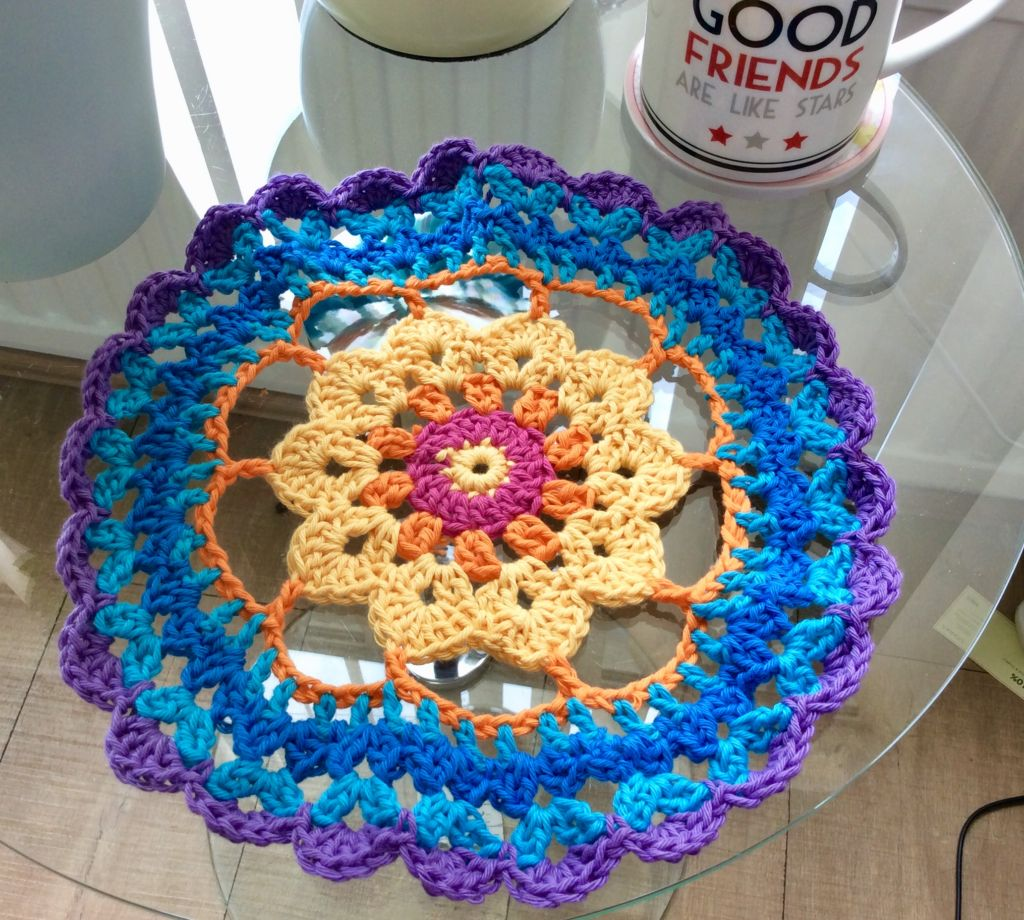 Crochet mandala in summer blues and sunny orange colours.